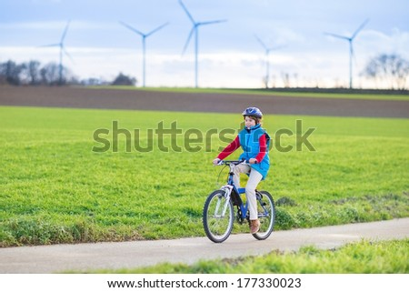Happy young teenager boy riding his bike in a beautiful European landscape with energy wind mills - stock photo