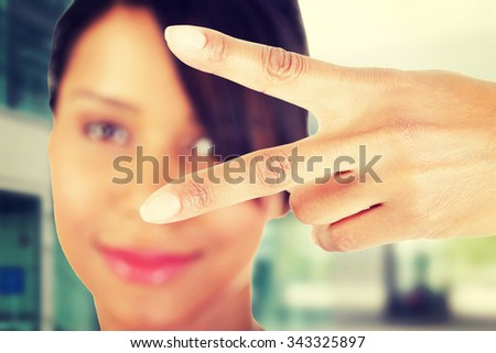 Happy young teenager girl showing victory sign. - stock photo