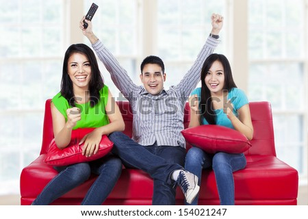 Happy young teenager watching football on tv at home - stock photo