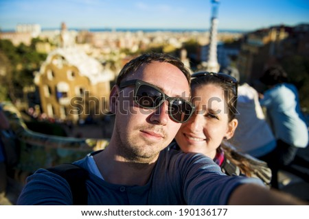 Happy young tourist couple looking at camera and taking selfie in Parc Guell, Barcelona, Spain. - stock photo