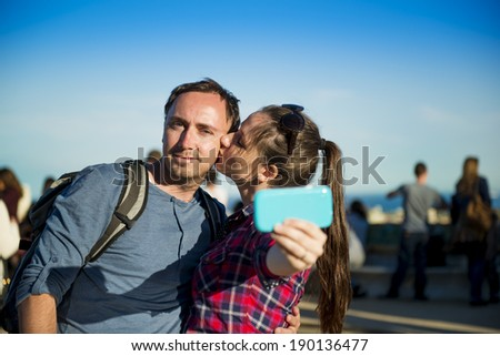 Happy young tourist couple looking at camera and taking selfie, smiling and having fun on Europe vacation trip in Barcelona, Spain. - stock photo
