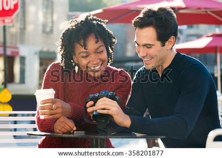 Happy young tourist couple looking at pictures in their camera in a cafe. Smiling couple looking at their photos on the screen of camera in the cafe outdoor. Multi ethnic couple sitting at cafeteria. - stock photo