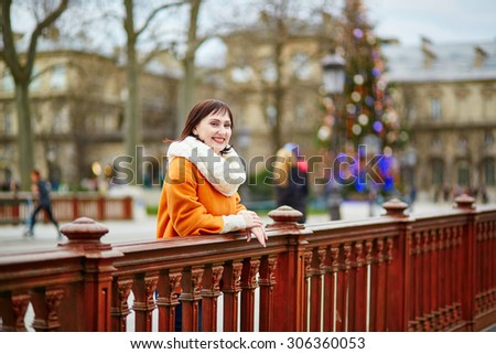 Happy young tourist in Paris on a winter day, main Parisian Christmas tree and Notre-Dame cathedral in the background - stock photo