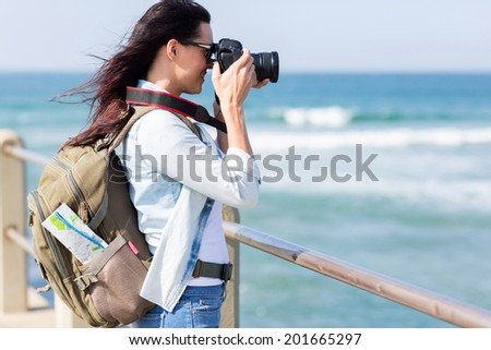 happy young tourist photographing at beach - stock photo