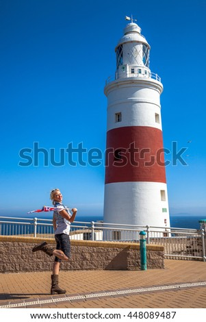 Happy young tourist woman waving a British flag. Europa Point Lighthouse on the southernmost point of Gibraltar. Gibraltar is a territory of South West Europe which is part of the United Kingdom. - stock photo