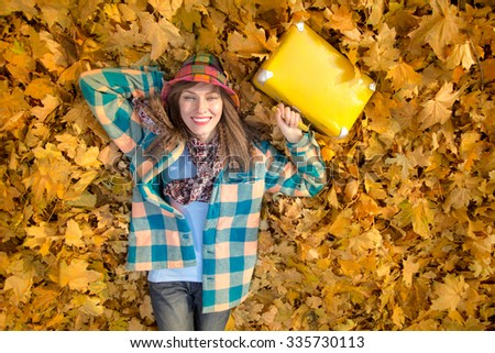 Happy young travel woman having fun lying on autumn fallen yellow leaf background. concept - stock photo