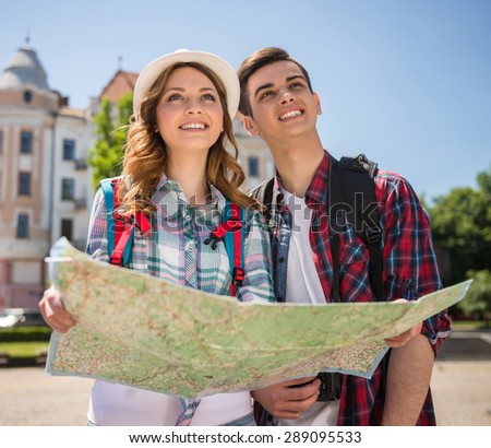 Happy young travelers sightseeing city with map. Front view. - stock photo