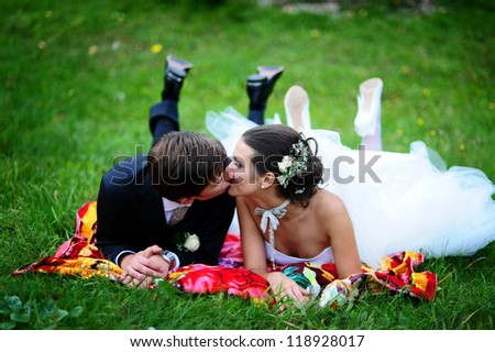 Happy young wedding couple on picnic kissing in park - stock photo