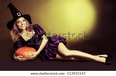 happy young  witch with  a pumpkin, against yellow studio background - stock photo