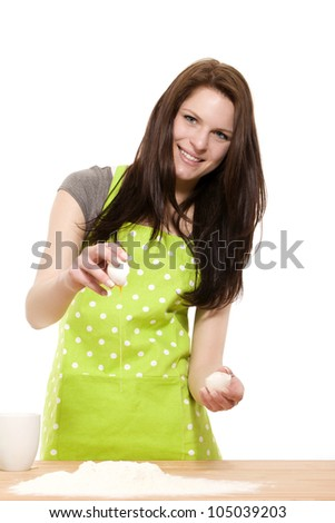 happy young woman adding an egg to flour for baking on white background - stock photo