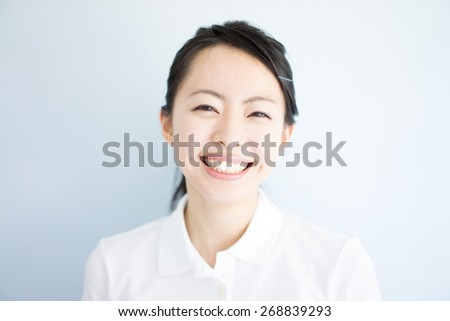happy young woman against light blue background - stock photo