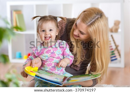 Happy young woman and child girl watching a baby booklet - stock photo