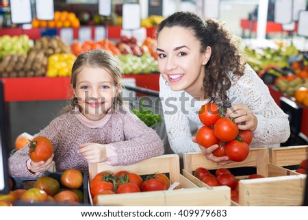 Happy young woman and girl buying red tomatoes in supermarket - stock photo