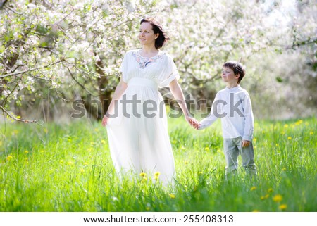 Happy young woman and her child in blooming apple garden - stock photo