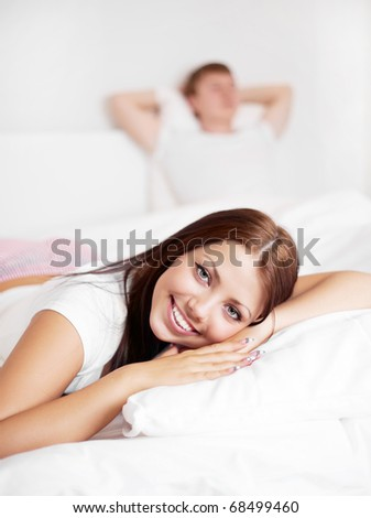 happy young woman and  sleeping man on the bed at home (focus on the woman) - stock photo