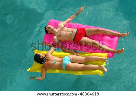 Happy young woman and the man floating on a mattress in water pool - stock photo