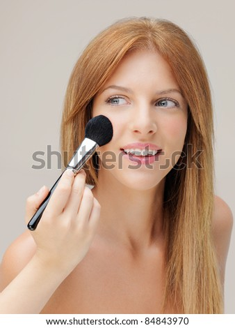 happy young woman applying blusher on cheeks - stock photo