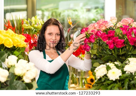 Happy young woman arranging flowers florist shop colorful roses - stock photo