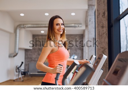 Happy young woman at gym doing cardio workout - stock photo