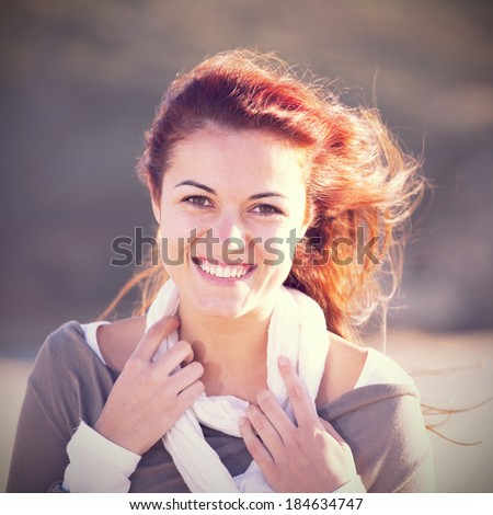 Happy young woman at the beach enjoying the sunny day - stock photo