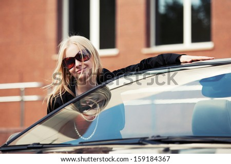 Happy young woman at the car - stock photo