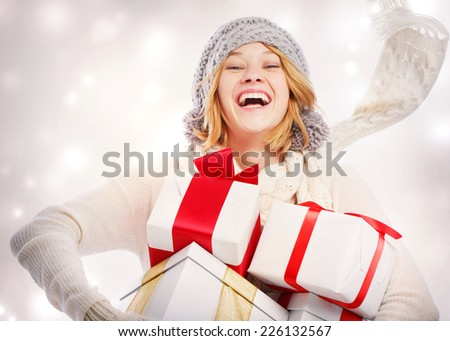 Happy young woman carrying Christmas presents  - stock photo