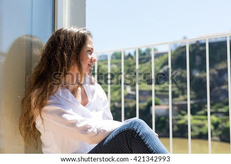 Happy young woman catching some sun at the balcony - stock photo
