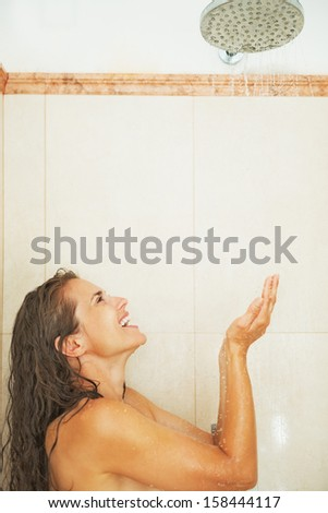 Happy young woman catching water drops in shower - stock photo