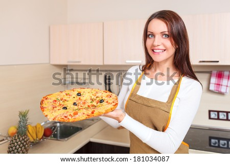 Happy Young Woman Cooking Pizza at Home. Oven - stock photo