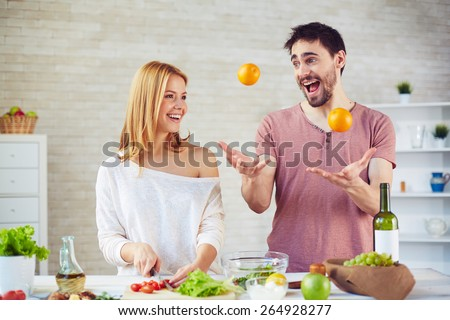 Happy young woman cooking salad in the kitchen, handsome man juggling oranges near by - stock photo
