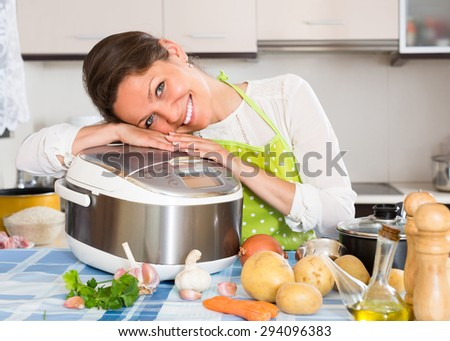 Happy young woman cooking with new multicooker in home interior - stock photo