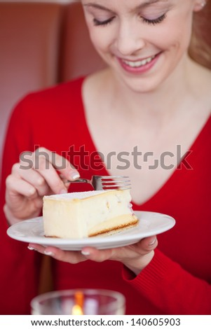 Happy young woman cutting pastry with fork in coffee shop - stock photo