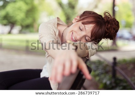 Happy young woman daydreaming on a park bench resting her head on her outstretched arms with a smile and her eyes closed - stock photo
