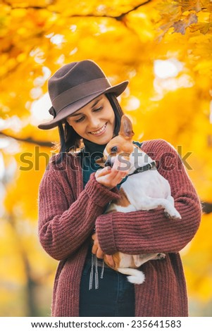 Happy young woman dog outdoors in autumn - stock photo