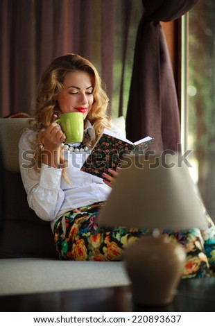 Happy young woman drinking coffee and reading book on couch near the window at home - stock photo