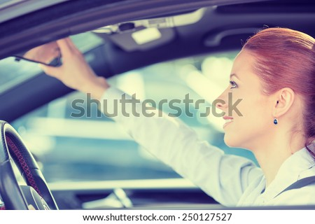 Happy young woman driver looking adjusting rear view car mirror, making sure line is free visibility is good before making turn. Human facial expressions, emotions. Safe trip, journey driving concept - stock photo