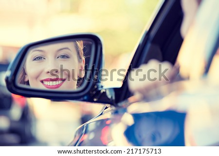 Happy young woman driver looking in car side view mirror, making sure line is free before making a turn. Human facial expressions, emotions. Safe trip, journey driving concept - stock photo