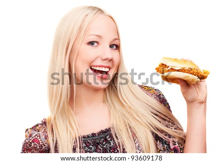 happy young woman eating a hamburger with chicken, isolated against white background - stock photo