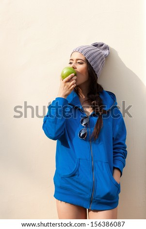 Happy Young Woman Eating Apple near yellow Wall. Diet. Dieting concept. Healthy food. Outdoors - stock photo
