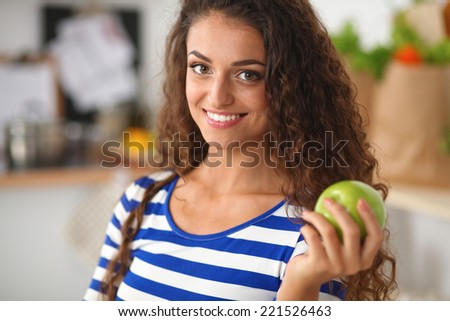Happy young woman eating apples on kitchen - stock photo