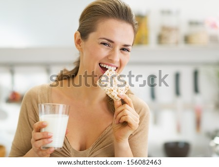 Happy young woman eating crisp bread with milk in kitchen - stock photo