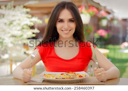 Happy Young Woman Eating Pizza  - Beautiful girl eating pizza in a restaurant    - stock photo