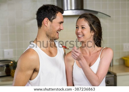Happy young woman feeding breakfast to her man in kitchen - stock photo