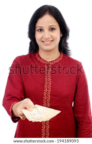 Happy young woman giving Indian currency against white background - stock photo