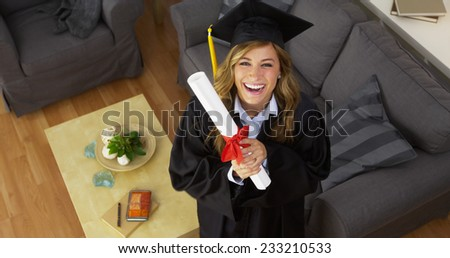 Happy young woman graduate holding diploma - stock photo