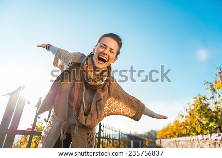 Happy young woman having fun time in autumn outdoors - stock photo