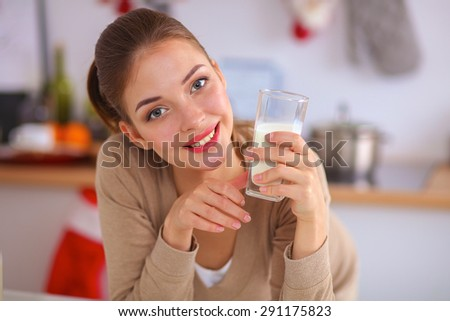 Happy young woman having healthy breakfast in kitchen - stock photo