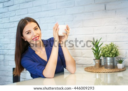 Happy young woman  holding a cup of coffee at home. - stock photo