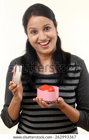 Happy young woman holding an open gift box against white - stock photo