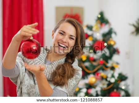 Happy young woman holding Christmas ball in front of Christmas tree - stock photo